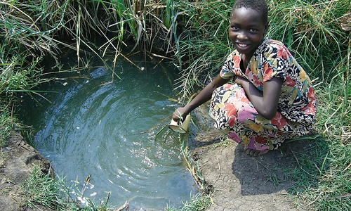 Young girl from Chise drawing water from a stagnent pool
